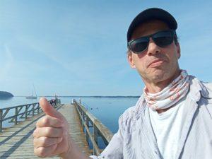 Harald mit Daumen hoch am Fördesteig, im Hintergrund Holzsteg und Ostsee